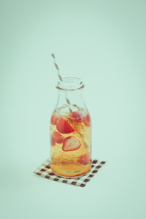 tea filter: Iced strawberry tea in glass bottle with striped straw with film filter effect Stock Photo