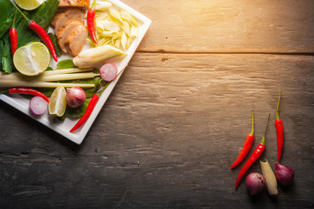 Ingredients set for Thai spicy soup (Tom-yum) include lemon, galangal, red chili, red onion, lemongrass, and kaffir lime leaf on wood table in low key morning scene with blank copyspace area for text or message Stock Photo