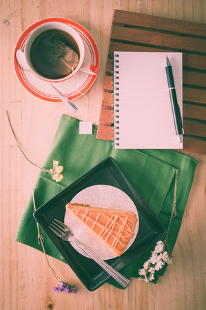 tea filter: a piece of Thai tea cake on black ceramic dish with a cup of hot tea and notepad on wood table in afternoon with film filter effect