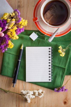 Opened notepad with pen and a cup of hot tea on wood table in cafe with morning scene Stock Photo - 46056889