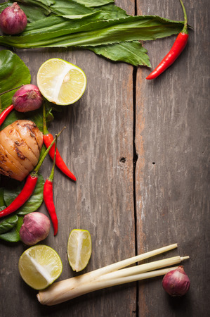 rustic food: Ingredients set for Thai spicy soup (Tom-yum) include lemon, galangal, red chili, red onion, lemongrass, and kaffir lime leaf on wood table in morning scene with blank area for text or message