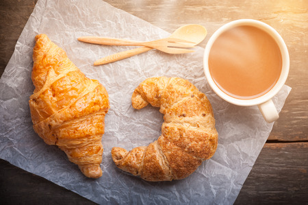 morning breakfast: Butter croissant and whole wheat croissant on wood table with morning scene Stock Photo