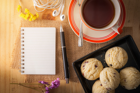 business book: Opened notepad with pen, cookies in black ceramic dish, small earphone, and a cup of hot tea on wood table in cafe with morning scene Stock Photo