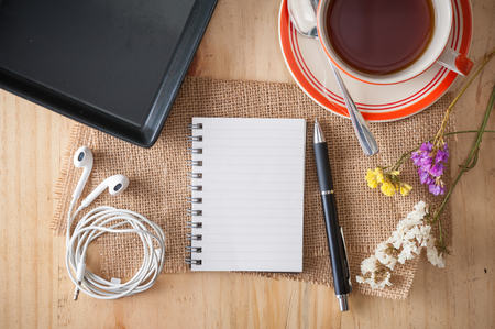 pad and pen: Opened notepad with pen, empty black ceramic dish, small earphone, and a cup of hot tea on wood table in cafe with morning scene Stock Photo