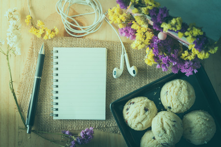 tea filter: Opened notepad with pen, cookies in black ceramic dish, small earphone, and a cup of hot tea on wood table in cafe with film filter effect Stock Photo