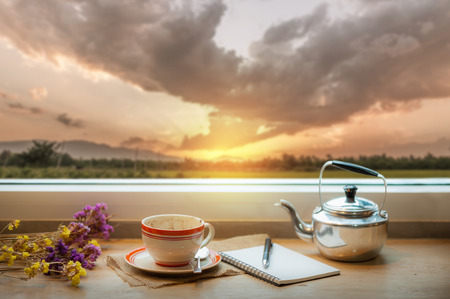 sunrise: Coffee cup and opened notebook, and pen on wood bar beside window at coffee shop in morning time with nature view of sunrise