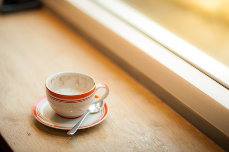 tarde de cafe: Coffee cup on wood bar beside window at coffee shop in afternoon time