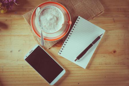 tarde de cafe: Libreta abierta con el �rea en blanco para el texto o mensaje, pluma, tel�fono inteligente, y una taza de caf� caliente en la mesa de madera en el tiempo de la tarde con efecto de filtro de cine