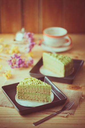 tea filter: Green tea cake in black ceramic dish on wood table in afternoon time with film filter effect