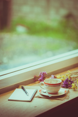 tarde de cafe: Coffee cup, opened notebook, and pen on wood bar beside window at coffee shop in afternoon time