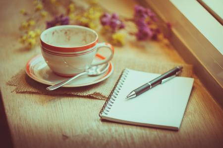 tarde de cafe: Taza de caf�, cuaderno abierto y la pluma en la barra de madera junto a la ventana en la cafeter�a en el tiempo de la tarde con efecto de filtro de cine