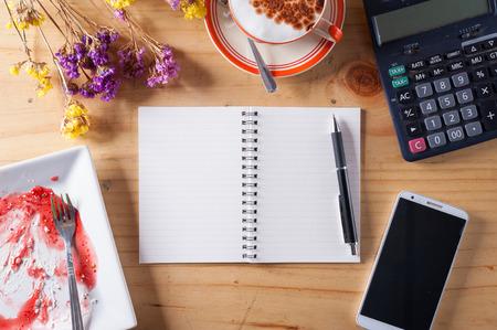 calculadora: Cuaderno abierto con el �rea en blanco para el texto o mensaje, pluma, tel�fono inteligente, el plato de postre sucio, y la calculadora en la mesa de madera en el tiempo por la tarde