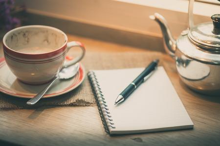 tarde de cafe: Cuaderno abierto, la pluma y la taza de café en la barra de madera en la tienda de café en el tiempo de la tarde con efecto de filtro de cine Foto de archivo