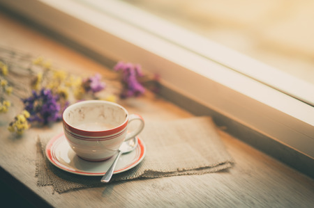 tarde de cafe: Coffee cup on wood bar beside window at coffee shop in afternoon time with film filter effect
