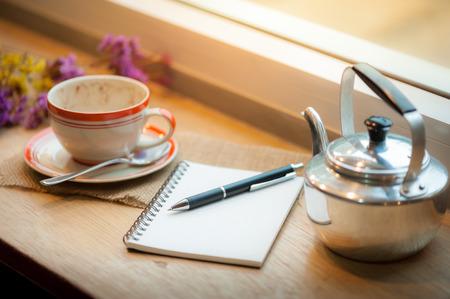 afternoon cafe: Cuaderno abierto, la pluma y la taza de café en la barra de madera en la tienda de café en el tiempo por la tarde