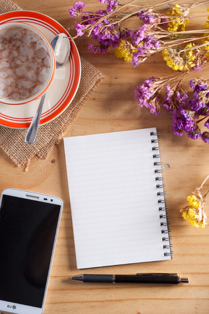 tarde de cafe: Opened notepad with blank area for text or message, pen, smart phone, and a cup of hot coffee on wood table in afternoon time