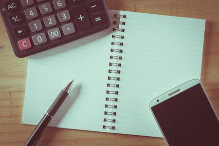 calculadora: Libreta abierta con el �rea en blanco para el texto o mensaje, pluma, tel�fono inteligente y calculadora en tabla de madera con efecto de filtro de cine