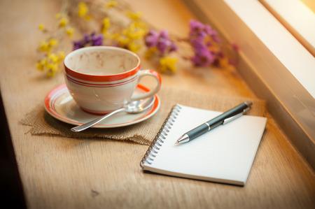 tarde de cafe: Taza de caf�, cuaderno abierto y la pluma en la barra de madera junto a la ventana en la cafeter�a en el tiempo por la tarde Foto de archivo