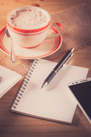 tarde de cafe: Opened notepad with blank area for text or message, pen, smart phone, and a cup of hot coffee on wood table in afternoon time with film filter effect Foto de archivo