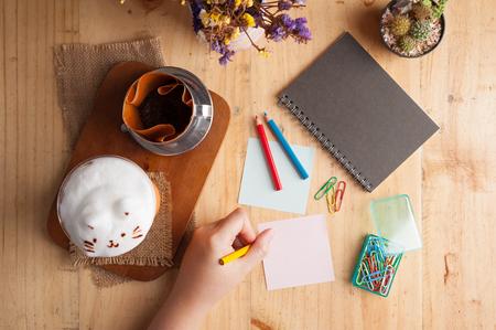 lapiz y papel: Escritura de la mujer de la mano izquierda en el papel pegajoso con espacio en blanco para el texto o un mensaje en la mesa de madera con el cuaderno, clip de papel, lápiz de color, y la pluma en el café