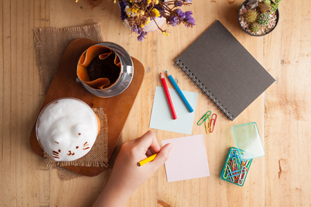 left hand: Woman left hand writing on sticky paper with blank space for text or message on wood table with notebook, paper clip, color pencil, and pen in cafe Stock Photo