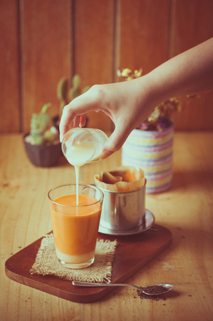 tea filter: Woman right hand pouring fresh milk into glass of Dripped Thai tea by Vietnamese style on wood table in cafe with vintage filter effect Stock Photo