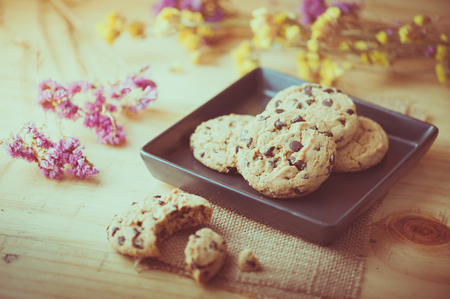 chocolate chips cookies: Chocolate chip cookies in black ceramic dish at cafe in morning time with vintage filter effect
