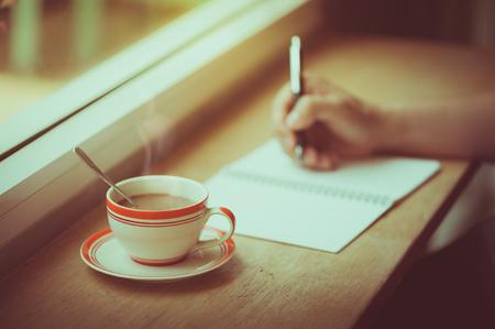 afternoon cafe: Una taza de café en la barra de madera junto a la ventana en café con la escritura de la mano derecha masculina en el cuaderno en el tiempo de la mañana con efecto de filtro de película de época Foto de archivo