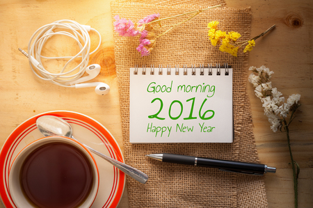 """tarde de cafe: """"Buenos d�as 2016 Feliz a�o nuevo"""" se escribe en la libreta abierta con la pluma, peque�o aud�fono, y una taza de t� caliente en la mesa de madera en caf� con la escena de la ma�ana Foto de archivo"""