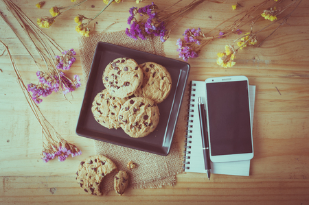 circuito integrado: galletas de chocolate en un plato de cerámica negro con el teléfono inteligente, cuaderno y una pluma en el café en tiempo de la mañana con efecto de filtro de la vendimia Foto de archivo