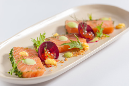 faked: Smoked salmon with herbs, beetroot, faked salmon roe (sauce cooked by molecular gastronomy technic) garnished with mago sauce and wasabi mayo Stock Photo