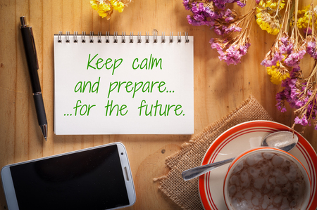 tarde de cafe: Keep calm and prepare for the future is written on notepad with pen, smart phone, and a cup of hot coffee on wood table in afternoon time