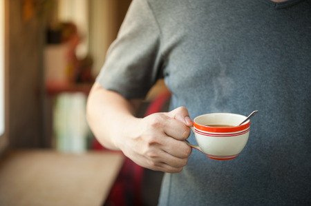 tarde de cafe: The man wearing grey t-shirt holding coffee cup in his right hand in afternoon time Foto de archivo