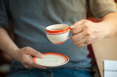 tarde de cafe: El hombre que llevaba una camiseta gris que sostiene la taza de caf� en la mano en el tiempo por la tarde Foto de archivo