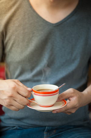 tarde de cafe: The man wearing grey t-shirt holding coffee cup in his hand in afternoon time