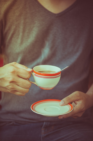 tarde de cafe: The man wearing grey t-shirt holding coffee cup in his hand in afternoon time with film filter effect