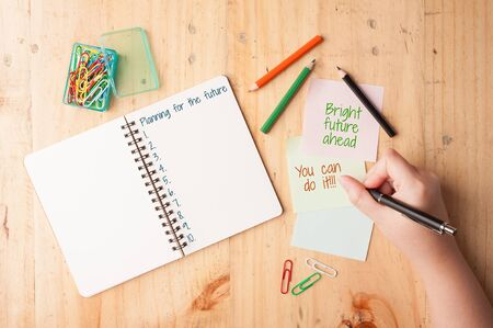 """nota de papel: Mujer escritura de la mano derecha """"brillante futuro por delante que puede hacerlo"""" en el cuaderno y papel pegajoso con el clip de papel, lápiz de color, y el lápiz sobre la mesa de madera"""
