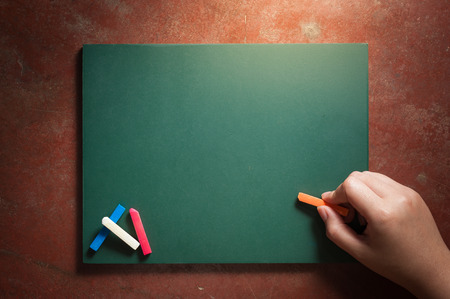 Woman right hand writing on small black board in green color with blank space for text or message with low key scene