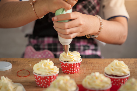 red velvet: The action of making red velvet cupcakes. Woman hand piping cream cheese on cupcake. Stock Photo