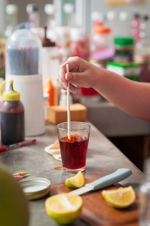 dissolve: The process of making Thai lemon tea. Woman right hand stir hot tea to dissolve and mix ingredients together. Stock Photo