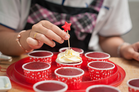 stab: The action of making red velvet cupcakes. Woman hand stab down star shape fondant on cupcake Stock Photo