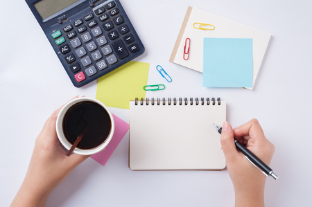blank space: Woman right hand writing on small notepad with blank space for text or message beside sticky paper, calculator, and take away coffee cup on office table while another hand holding coffee cup
