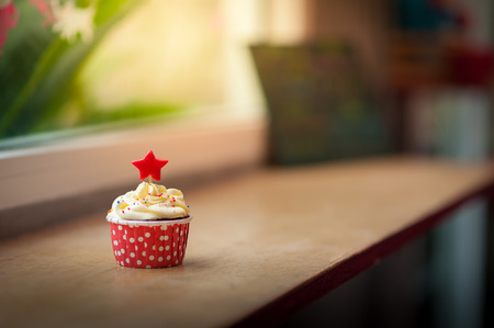 red velvet cupcake: Small red velvet cupcake with cream that made from yogurt and cream cheese garnished with star shape fondant and colourful sugar sprinkle on wood bar in cafe in morning time with low key scene