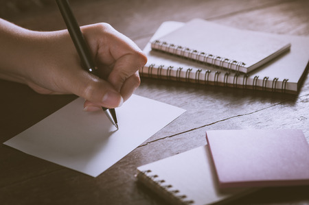 blank page: Woman left hand writing on blank paper on wood table with notebooks on wood table with low key scene and vintage filter effect