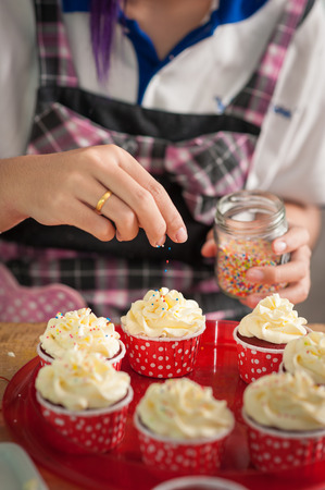 adding sugar: The action of making red velvet cupcakes. Woman hand adding sugar sprinkle on cupcake.