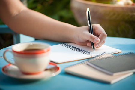 Woman left hand writing journal on small notebook in outdoor area at cafe with morning scene