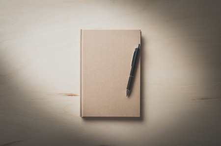 hard cover: Closed hard cover notebook with blank area on front cover on wood table in morning time with film filter effect