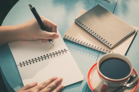 Vrouwenlinker schrijvend dagboek op klein notitieboekje op openluchtgebied bij koffie met ochtendscène en uitstekend filtereffect