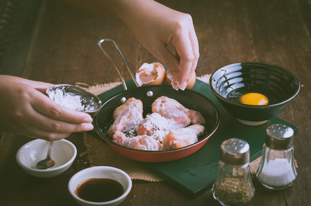 lady hand: Preparation for cooking in home kitchen. Woman keft hand put corn flour into fry pan to mix with chicken wings with vintage filter effect.