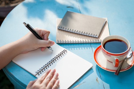 Woman left hand writing journal on small notebook in outdoor area at cafe with morning scene Stock Photo - 55796065